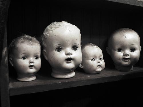 image of 4 doll heads on a shelf