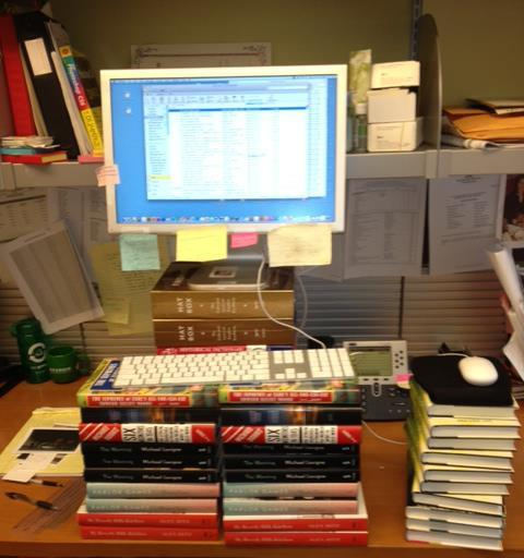 A photograph of stacked books raising the level of a computer to create an impromptu standing desk.