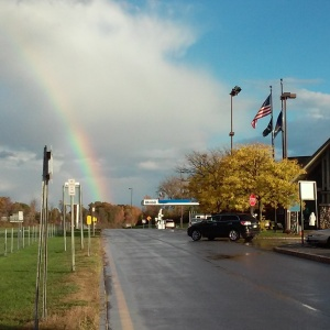 "Photo titled ""The Road Ahead"" by Arden Kirkland. A view of the road at a NY state thruway stop, leading straight to a rainbow in the distance."