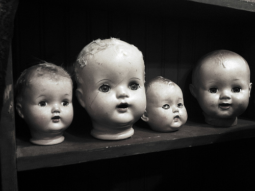 image of 4 doll heads on a shelf